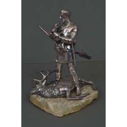 Apsudrabotas bronzas figūra uz akmens pamatnes